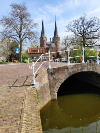 Vue de Oostpoort de Delft depuis un canal
